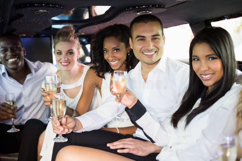 Well ubierał ludzi pije szampana w limuzynie zdjęcia royalty free