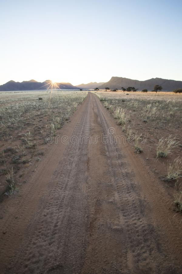 Well used, Dusty desert road to nowhere. Southern Namibia. Mountain scenery surrounding. Star sun. stock images