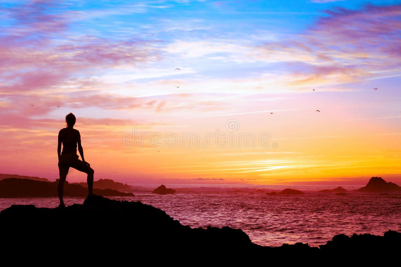 Wellbeing concept. Silhouette of person enjoying beautiful sunset with view of ocean stock photo