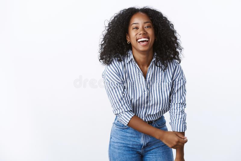 Wellbeing happiness people concept. Entertained charming friendly carefree african american woman curly-haired bending. Towards camera having fun playful mood royalty free stock images