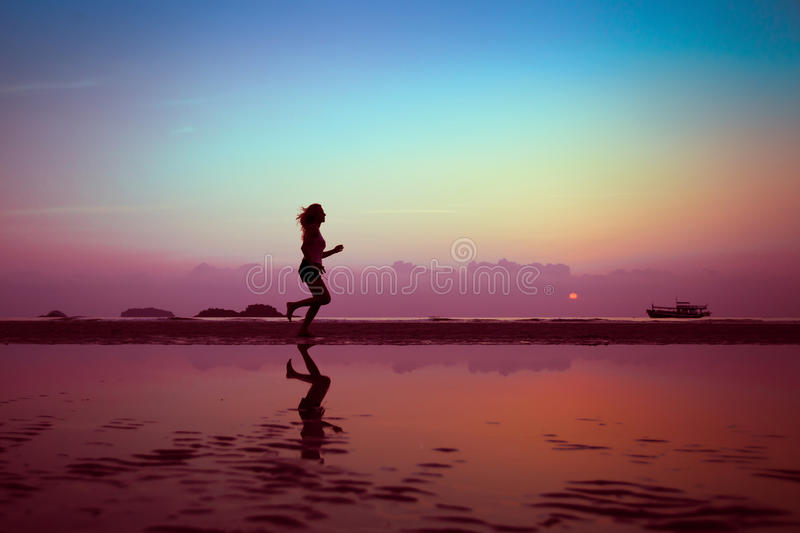 Wellbeing or sport background. Woman silhouette on the beach stock photo