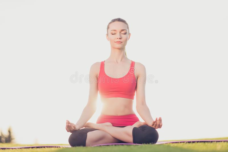 Wellbeing, wellness, vitality, peace lifestyle. Young calm woman. Is practicing yoga in the lotus position in the spring park outdoors, in trendy sports outfit stock image