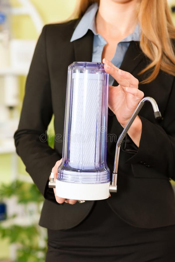 Welldressed kobieta trzyma nowożytnego faucet zbiornika zdjęcia stock