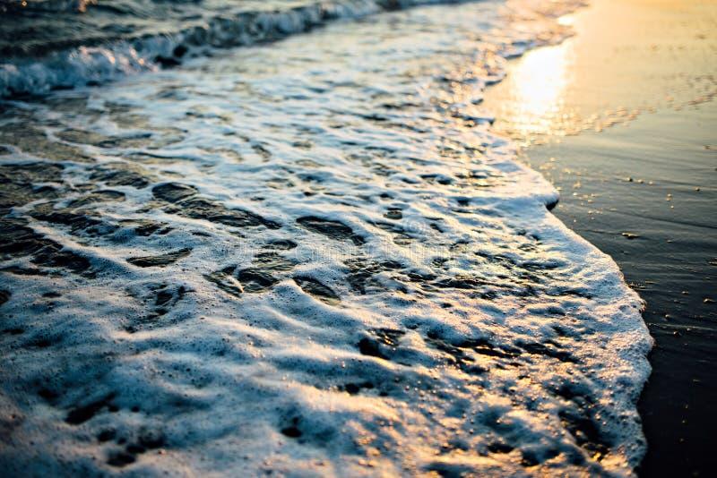 Welle des Ozeanmeeres auf dem Sandstrand am Sonnenunterganglicht stockfotografie