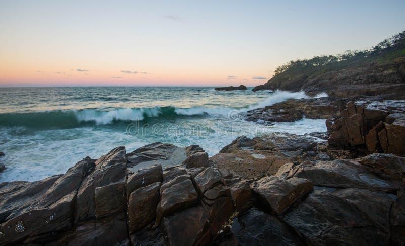 Welle, die über Felsen zusammenstößt stockfotografie