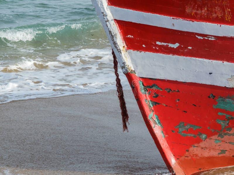 Welle, die über verlassenem rotem Bootsstamm bricht lizenzfreie stockbilder