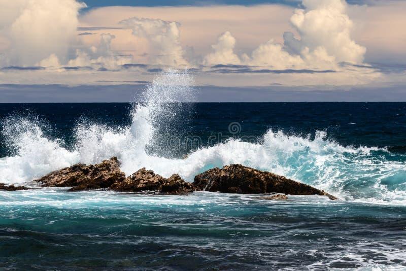 Welle, die auf dunklem Lavafelsen zusammenstößt; weißer Spray in der Luft-, Blauen/Grünenwelle zu einem Seiten-, dunklen Ozean un stockfoto