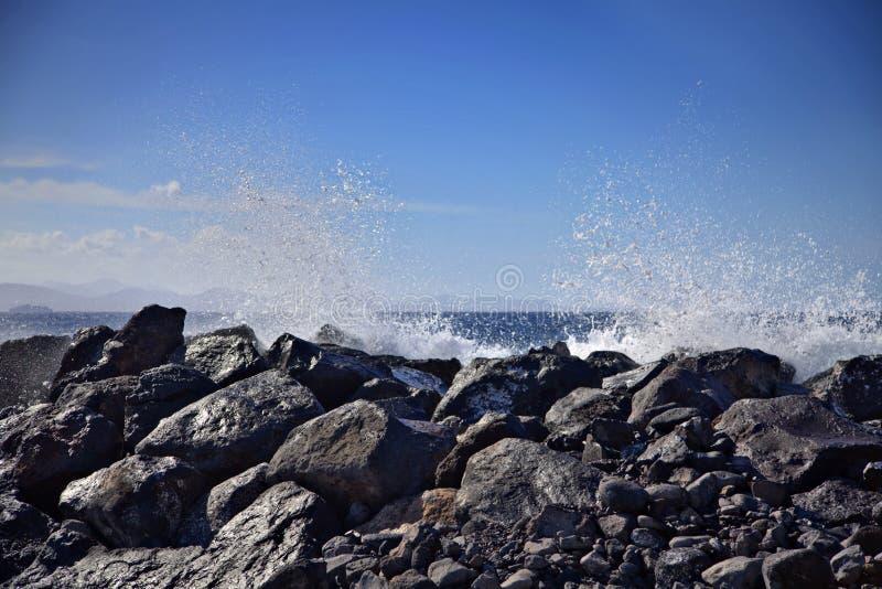 Welle, die Felsen mit blauem Himmel schlägt stockbild