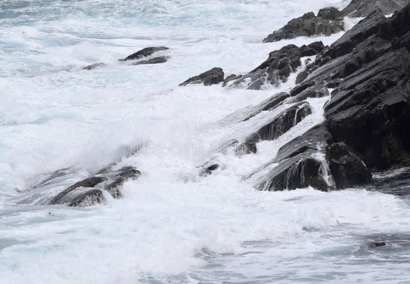 Welle, welche die schroffe Küstenlinie schlägt stockfotografie