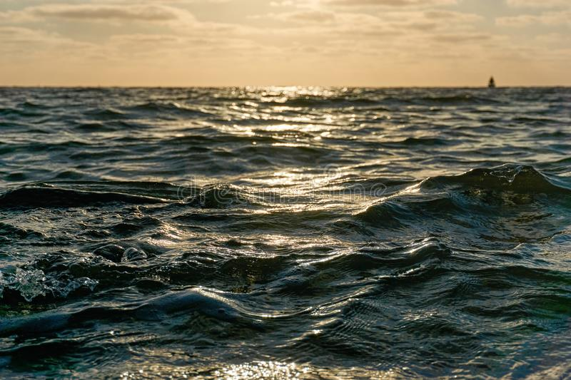 Wellen auf dem Meer bei einem orangefarbenen Sonnenuntergang stockfoto