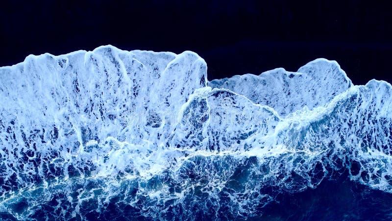 Wellen auf schwarzem Sand stockfotos