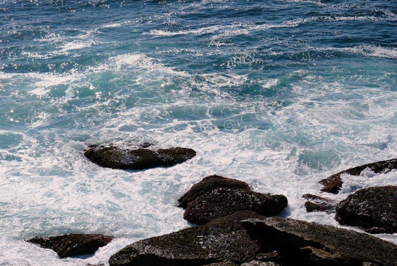 Wellen des Pazifischen Ozeans, die um Küstenfelsen, Australien wirbeln lizenzfreie stockfotos