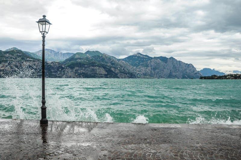 Wellen, die über der Pflasterung in dem Meer zusammenstoßen Berge im Hintergrund Große schwarze Lampe auf dem links stockbild
