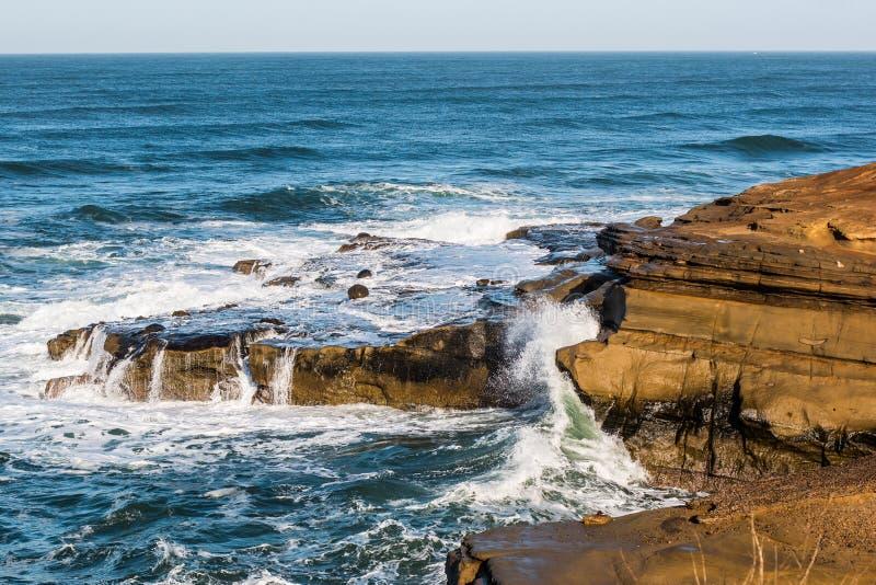 Wellen, die über Felsformationen an den Sonnenuntergang-Klippen zusammenstoßen stockbilder