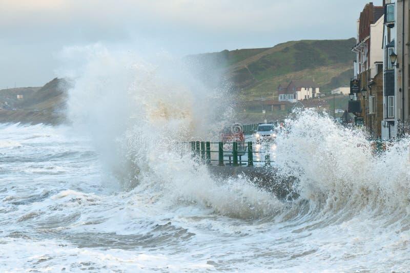 Wellen, die über Küstestraße spritzen lizenzfreies stockbild