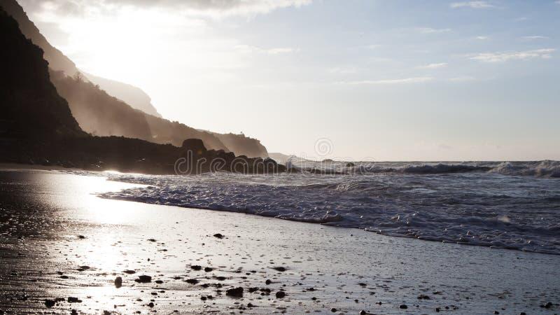 Wellen, die auf dem Ufer eines Teneriffa-Strandes mit Rücklicht des entgegenkommenden Sonnenuntergangs brechen stockbilder