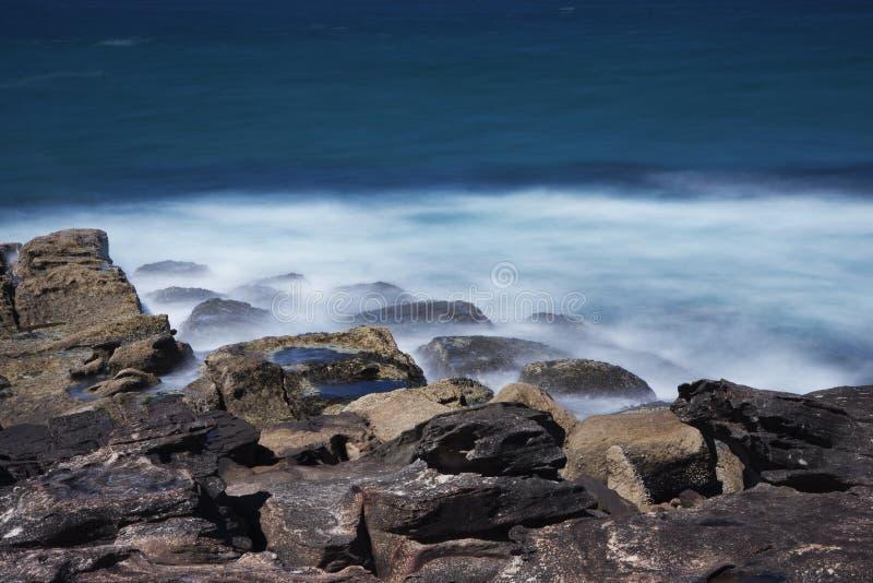 Wellen, die auf den Felsen des männlichen Strandes brechen stockfoto