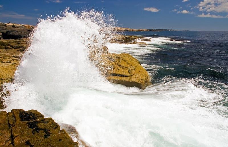 Wellen, die auf Felsen abbrechen stockbild