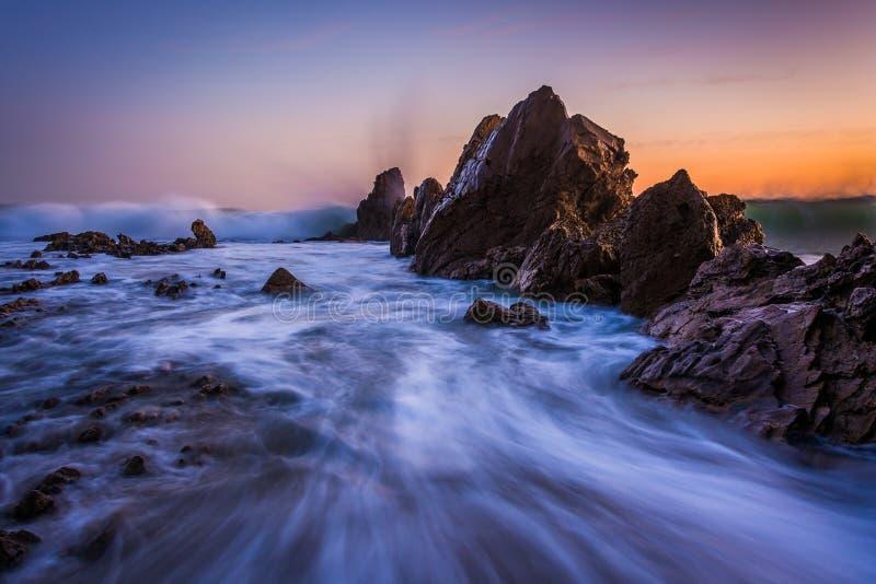Wellen, die auf Felsen bei Sonnenuntergang, in Corona del Mar zusammenstoßen lizenzfreie stockfotos