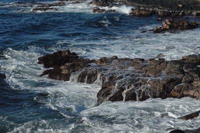 Wellen, die auf Felsen brechen stockfotografie