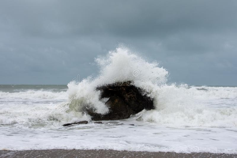 Wellen, die an einem kalten Wintertag über Felsen springen stockfotografie