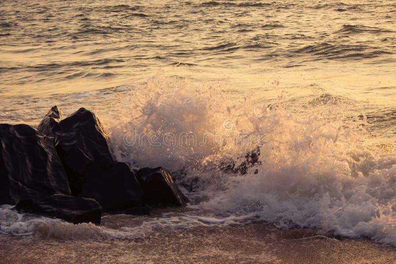 Wellen, die Felsen bei Sonnenuntergang schlagen stockfotos