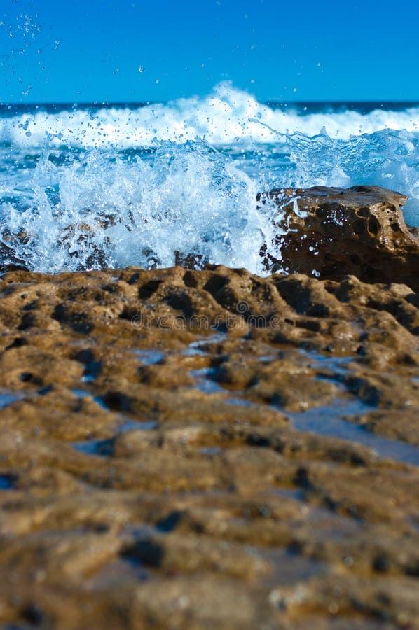 Wellen, die Felsen schlagen lizenzfreies stockbild
