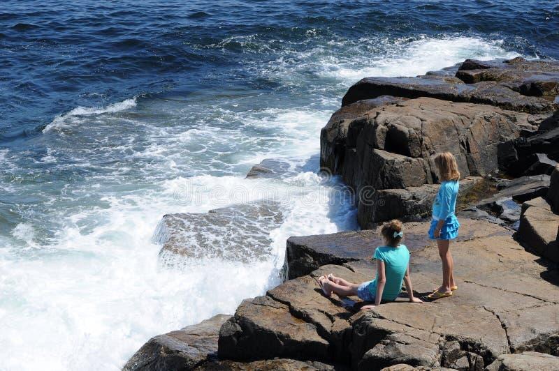 Wellen, die gegen Felsen zusammenstoßen stockfotos
