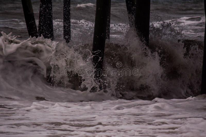 Wellen, die unter dem Pier zusammenstoßen stockfotos