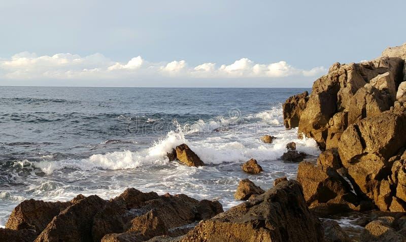 Wellen gegen Felsen stockfotografie
