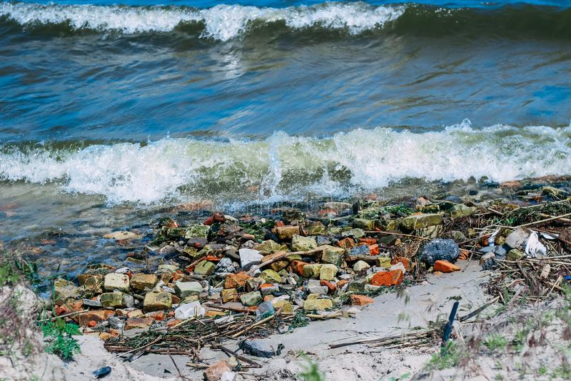 Wellen holen Steine und Gebäuderückstand zum Ufer lizenzfreies stockbild