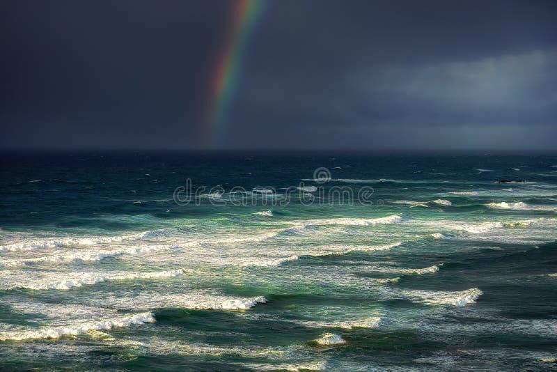 Wellen im rauen Meer mit stürmischen Wolken und Regenbogen lizenzfreie stockfotografie