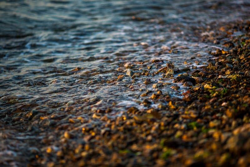 Wellen rollen auf kleinen Steinen w?hrend des Sonnenuntergangs stockfotografie