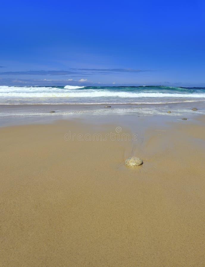 Wellen sondern Stein auf sandigem Strand mit Exemplarplatz aus stockfotos