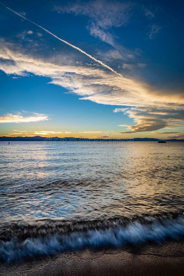 Wellen stoßen weich auf Seeufer-Strand bei Lake Tahoe mit den gelben und weißen Wolken und einem tiefen blauen Himmel während des stockfotografie