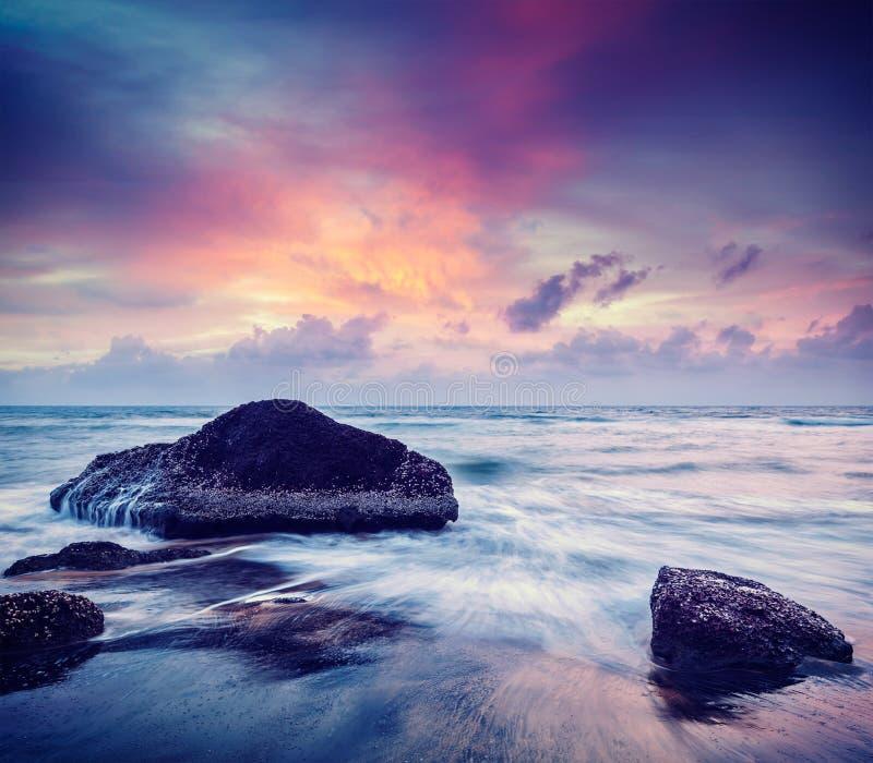 Wellen und Felsen auf Strand des Sonnenuntergangs stockfoto