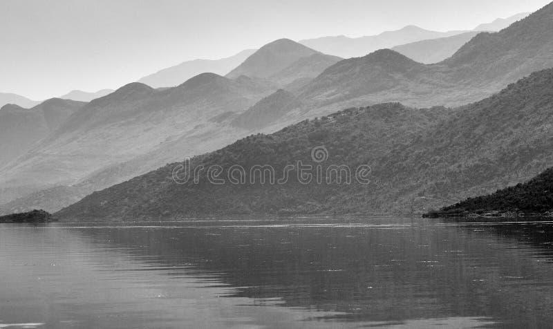 Wellenartig bewegende Berge über dem See stockbild
