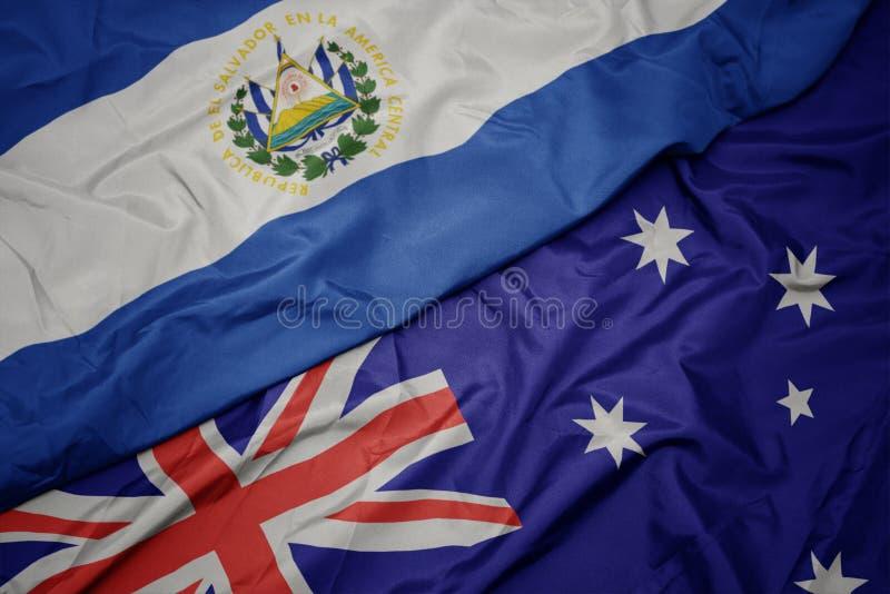wellenartig bewegende bunte Flagge von Australien und Staatsflagge von El Salvador lizenzfreie stockfotografie