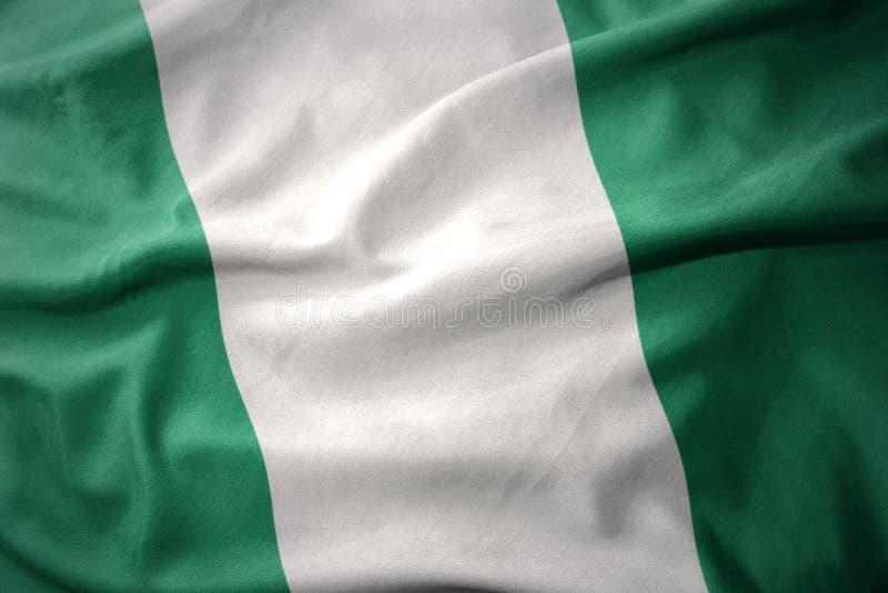 Wellenartig bewegende bunte Flagge von Nigeria stockfotografie