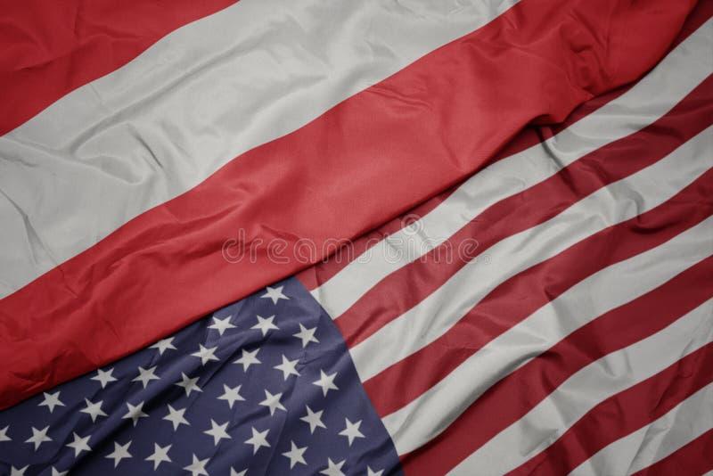 wellenartig bewegende bunte Flagge von Staaten von Amerika und Staatsflagge von Österreich lizenzfreies stockbild