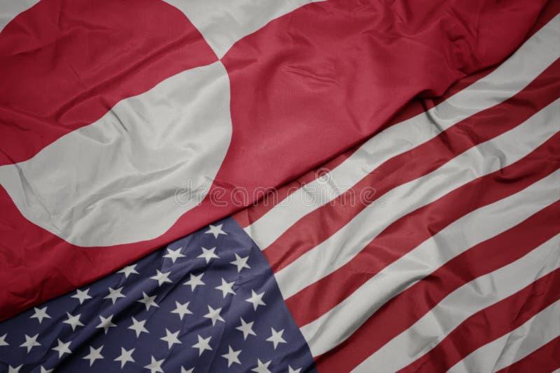 wellenartig bewegende bunte Flagge von Staaten von Amerika und Staatsflagge von Grönland lizenzfreie stockfotos