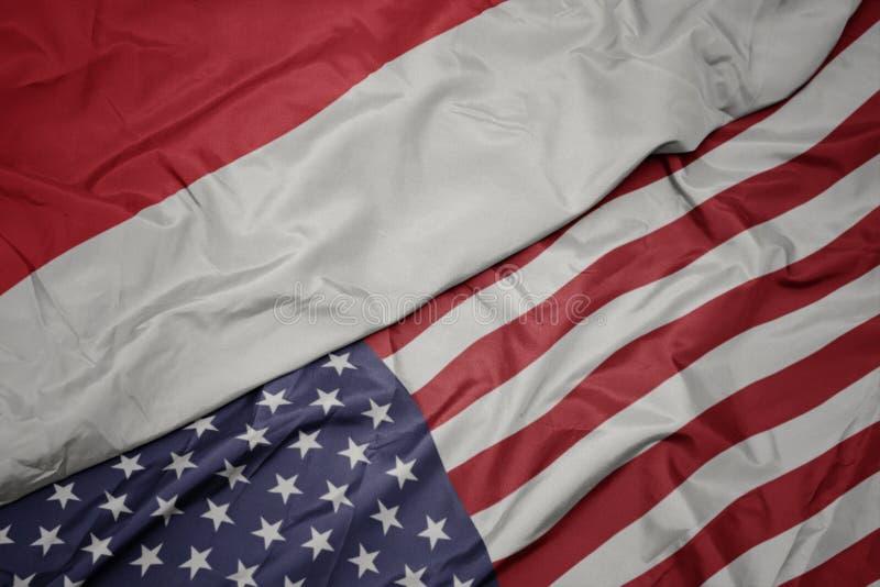 wellenartig bewegende bunte Flagge von Staaten von Amerika und Staatsflagge von Indonesien lizenzfreie stockfotos