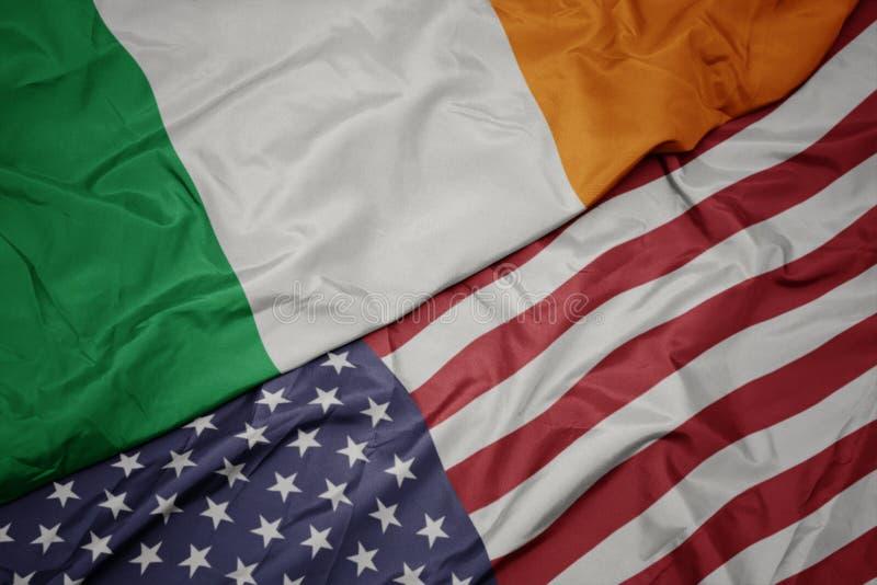 wellenartig bewegende bunte Flagge von Staaten von Amerika und Staatsflagge von Irland Makro lizenzfreies stockfoto