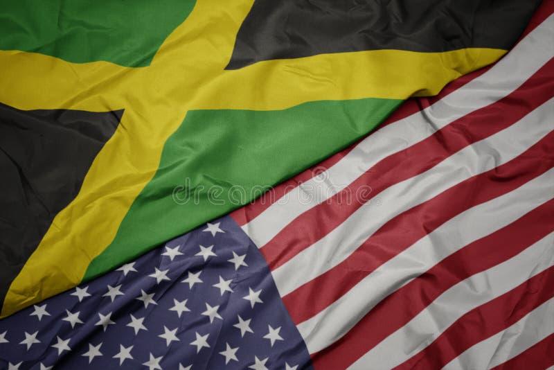 wellenartig bewegende bunte Flagge von Staaten von Amerika und Staatsflagge von Jamaika stockfoto