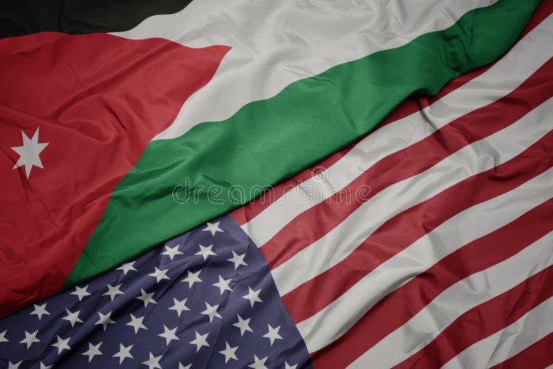 wellenartig bewegende bunte Flagge von Staaten von Amerika und Staatsflagge von Jordanien stockfotos