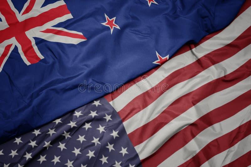 wellenartig bewegende bunte Flagge von Staaten von Amerika und Staatsflagge von Neuseeland lizenzfreies stockbild
