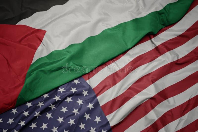 wellenartig bewegende bunte Flagge von Staaten von Amerika und Staatsflagge von Palästina stockbild