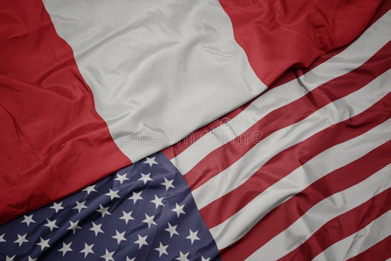 wellenartig bewegende bunte Flagge von Staaten von Amerika und Staatsflagge von Peru lizenzfreie stockfotos