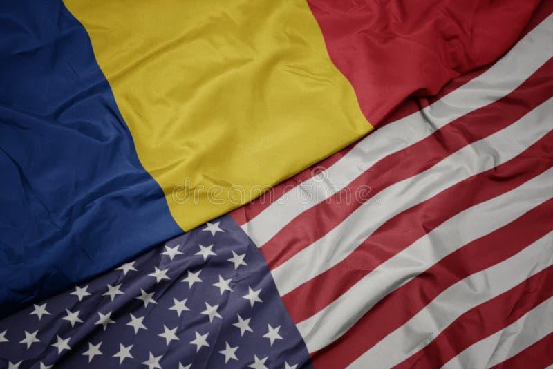 wellenartig bewegende bunte Flagge von Staaten von Amerika und Staatsflagge von Rumänien Makro stockfotografie