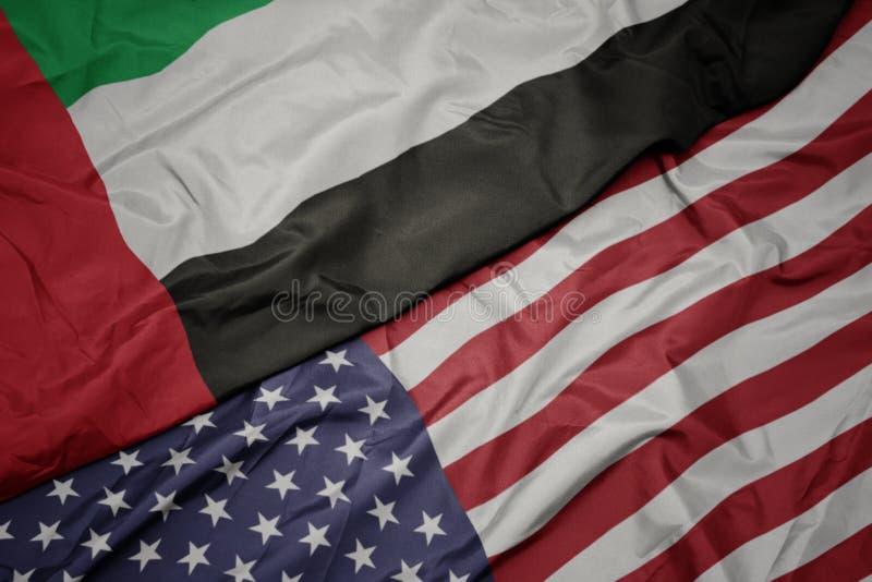 wellenartig bewegende bunte Flagge von Staaten von Amerika und Staatsflagge von Vereinigten Arabischen Emiraten stockfotografie